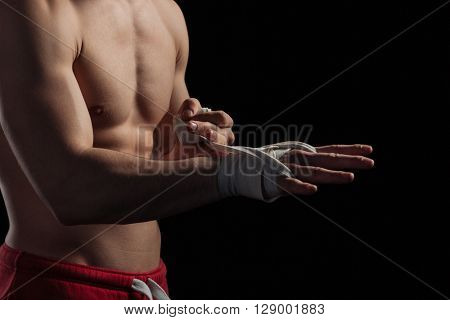 Cropped image of a male boxer preparing hands for fight over black background