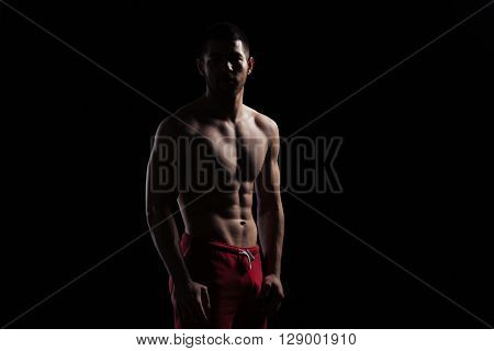 Silhouette of a fitness man standing over dark background
