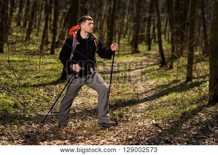 Hiker wearing hiking backpack and hardshell jacket on hike in forest. Man wearing hat gloves using hiking sticks poles outdoors in woods. Male hiker standing looking away.