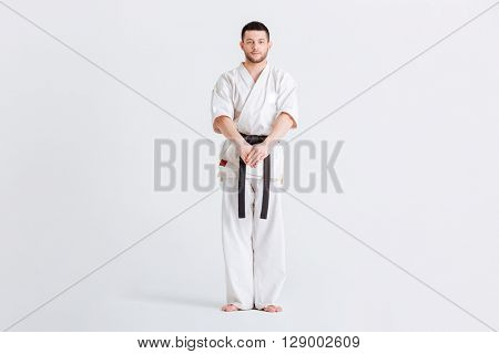 Full length portrait of a male fighter in kimono standing isolated on a white background