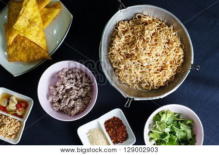 Ingredient spicy instant noodle with minced pork on wood background Top view