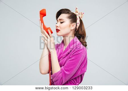 Sad attractive young housewife holding red telephone receiver