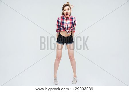 Full length of surprised pretty pinup girl standing with mouth opened
