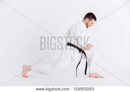 Full length portrait of a young man in kimono warming up isolated on a white background