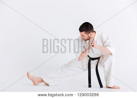 Young man in kimono stretching isolated on a white background