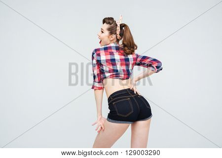 Back view of happy attractive pinup girl in checkered shirt and shorts