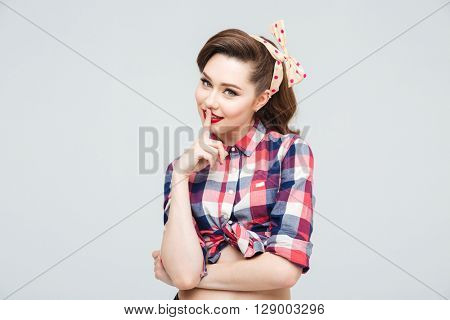 Portrait of cute smiling pinup girl showing silence gesture