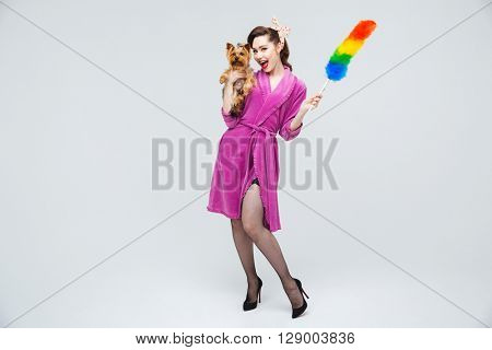 Smiling attractive young housewife standing and posing with dog and duster brush