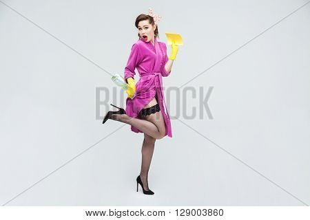 Full length of playful seductive young housewife in yellow rubber gloves with spray and duster