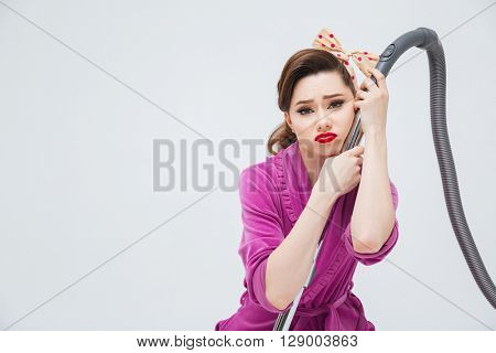 Portrait of exhausted upset young housewife with vacuum cleaner