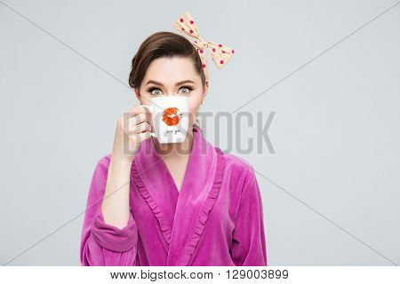 Funny cute young housewife hiding her face beahind a cup of tea