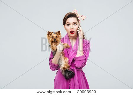 Shocked pretty young housewife holding dog and talking on cell phone