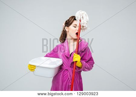Exhausted pretty young woman in yellow gloves holding basin with foamed detergent