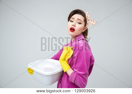 Tired upset young housewife in rubber gloves holding basin with foamed detergent