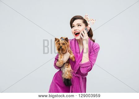 Cheerful surprised young housewife with dog talking on mobile phone