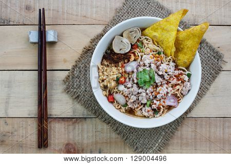 Spicy instant noodle soup with minced pork on wood background Top view