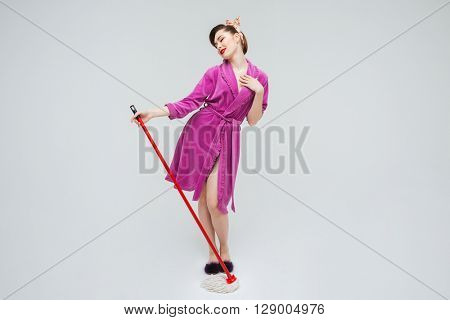 Smiling attractive young housewife posing and cleaning the floor with mop