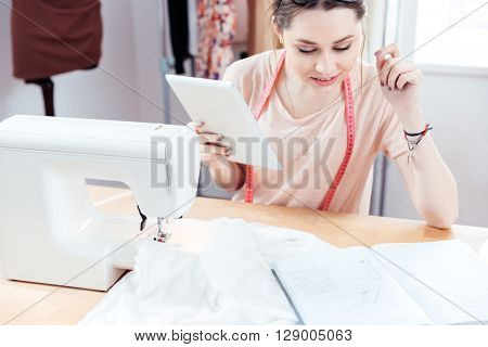 Concentrated cute young woman seamstress working and using tablet in workshop