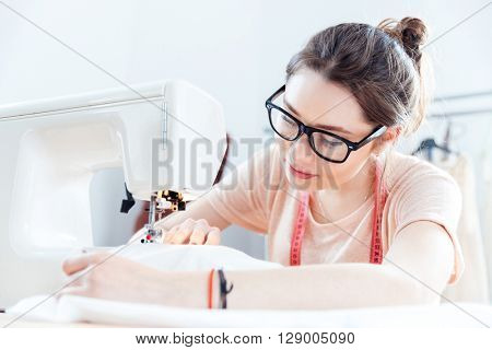 Serious cute young woman seamstress at work with cloth fabric