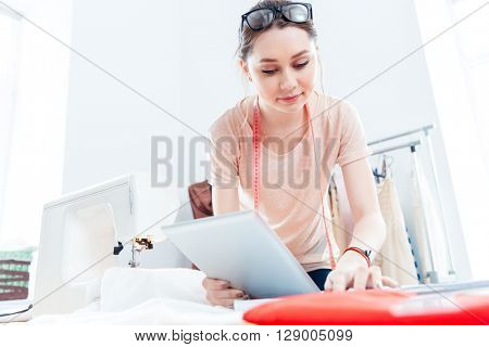 Serious beautiful young woman seamstress with tablet working and thinking in workshop