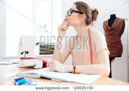 Beautiful pensive young woman seamstress working at the table and thinking