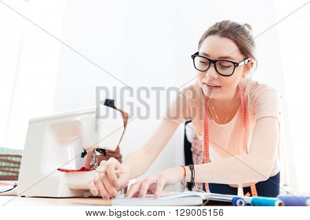 Concentrated pretty young woman seamstress in glasses standing and working in workshop