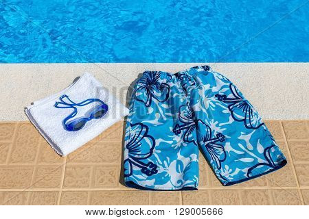 Blue swimming trunks goggles and bath towel at pool