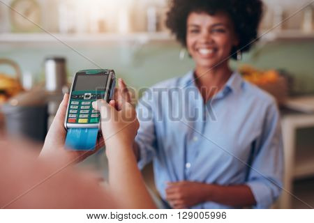 Female Customer Paying By Credit Card At Juice Bar
