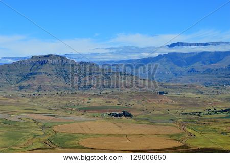 Drakensberg mountains with grass, trails and blue sky