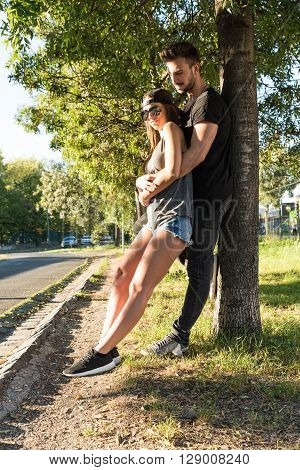 A young HipHop styled couple leaning to a tree during sunset in a urban environment.