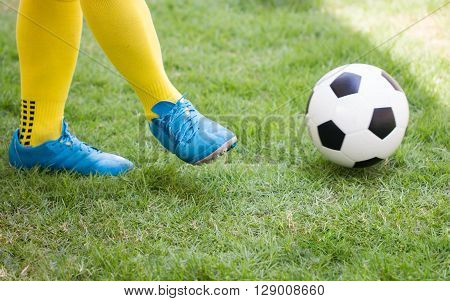 Athlete Kicking a soccer ball on field.