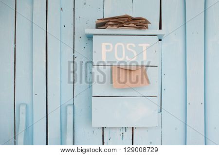 mailbox with letters in vintage style on wooden blue background.