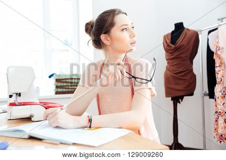Thoughtful cute young woman seamstress sitting and thinking in workshop