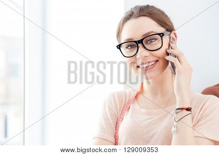 Closeup of smiling pretty young woman seamstress in glasses talking on mobile phone in studio