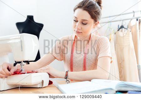 Concentrated beautiful young woman seamstress sews on the sewing machine and reading notes in notebook