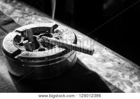 Cigarette On Stainless Ashtray.