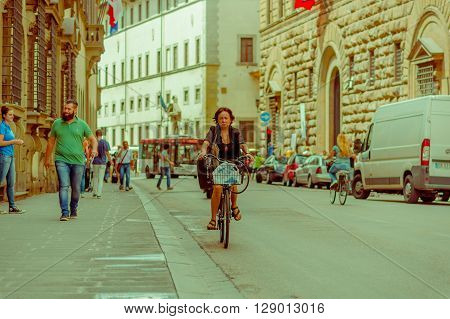 FLORENCE, ITALY - JUNE 12, 2015: Woman ridding a nice bycicle with a shopping bag, walkers on the side and a bus comming. Summer
