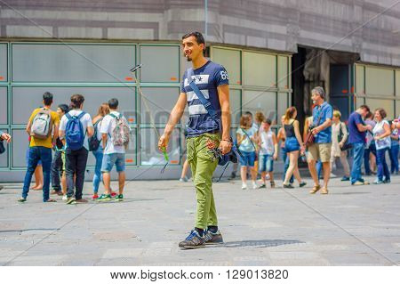 FLORENCE, ITALY - JUNE 12, 2015: In the middle of the street one selfie stick seller in green pants and blue shirt. Unidentified seller