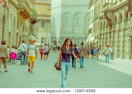 FLORENCE, ITALY - JUNE 12, 2015: Unidentified people walking in Florence street, turists visiting new buildings. Summer time.