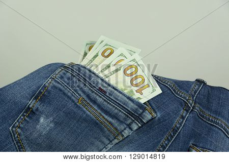 The money in the back pocket of blue jeans trousers