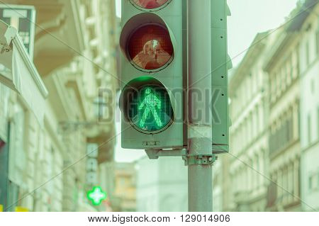 FLORENCE, ITALY - JUNE 12, 2015: Green sign that means, you can cross the street. Good manners