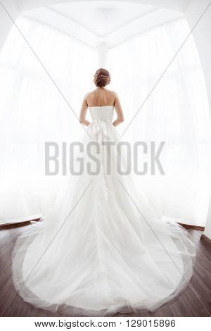 Beautiful young bride in white wedding dress indoors.  Luxuty model standing against big window at home. Girl waiting her groom in bright room. High key, made on fisheye lens photo.