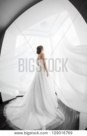 Beautiful young bride in white wedding dress indoors.  Luxuty model standing in full length against big window at home. Girl waiting her groom in bright room. High key, made on fisheye lens photo.
