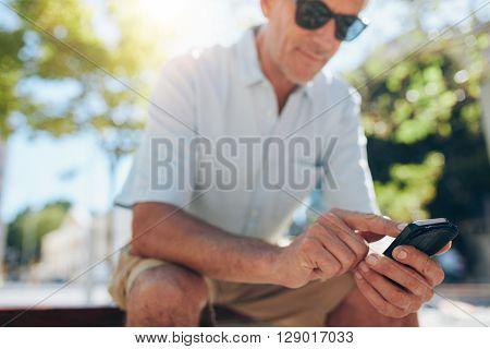 Senior Man Using Cell Phone Outdoors