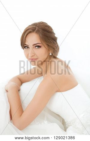 Beautiful young bride portrait in white wedding dress indoors.  Luxuty model sitting against big window at home. Girl waiting her groom and looking at camera in bright room. Beautiful wedding hairdress and make-up. High key photo.