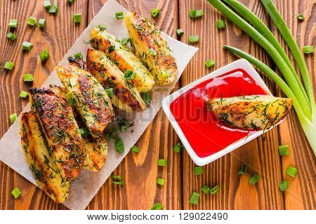 Fried Homemade Potato With Herbs And Ketchup On The Wooden Background