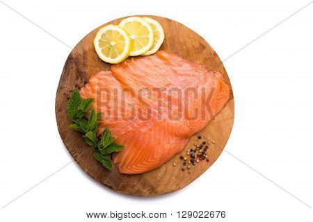 Salmon fillet with lemon pepper and mint on wooden board isolated on white background
