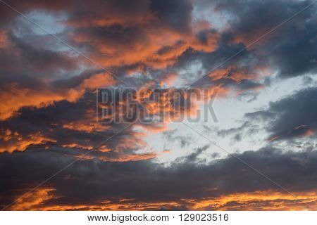 Dramatic sunset background  with stormy orange clouds