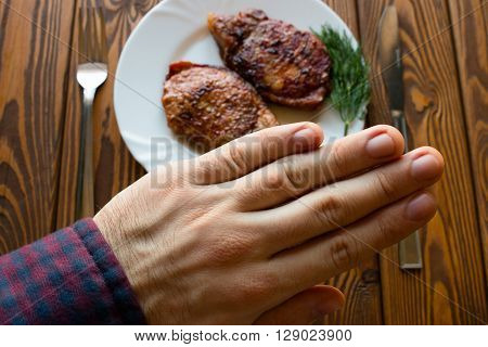 man refuses to grilled meat wooden background