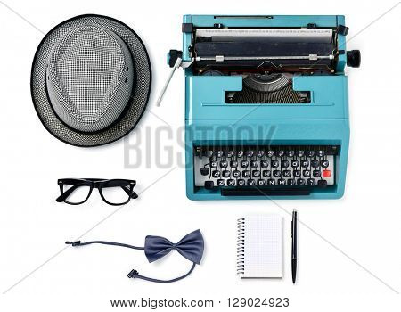 high-angle shot of a gray hat, an old blue typewriter, a pair of black plastic-rimmed eyeglasses, a gray bow tie, a notebook and a pen on a white background